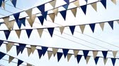 торжества : Panning shot of blue and white pennant flags on strings advertising a grand opening or celebration or event and flapping in the wind against a blue sky. Стоковые видеозаписи