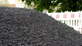 malzemeleri : Close up shot of a heap of black asphalt road surfacing material in a pile ready to be used on a road or street with safety barriers and trees in the background.