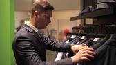 Man choosing business jacket from the raw in the shop. Vídeos