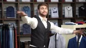 Young attractive man with a beard, dressed in a business suit, dancing in a mens clothing store.