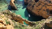portugalia : Lagos, Portugal - April 2018: Fishing boats on turquoise sea water at Ponta da Piedade, Algarve region, Portugal