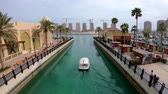medio oriente : Doha, Qatar - February 2019: Boat sailing into marina in residential area of The Pearl Qatar, close to Doha, an artificial island spanning nearly four million square meters.