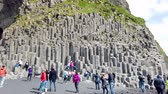 basalto : Vik, Iceland - August 2019: Unidentified tourists visiting black sand beach of Reynisfjara, mount Reynisfjall and the volcanic basalt columns in the southern coast of Iceland.