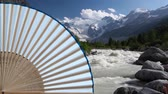 Typical Japanese hand fan made and wild river in the mountains