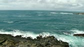 Churning Pacific Ocean with incoming tide breaking on basalt rocks.  Zoom out to view of  Depoe Bay