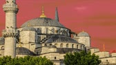ahmet : Sultan Ahmet Camii  Blue Mosque   glows in early evening light against dark clouds in the background Stock Footage