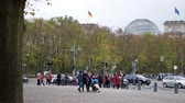 almanca : BERLIN, GERMANY - OCTOBER 26, 2018: Pan Shot of Tourists And Traffic Near German Reichstag Building In Berlin, Germany