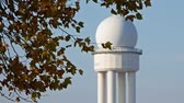 trafik : RRP 117 Radar Tower In Public City Park Tempelhofer Feld Behind Autumn Leaves In Berlin, Germany, Selected Focus Pan Shot