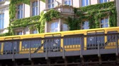 on : BERLIN, GERMANY - JUNE 24, 2019: Yellow BVG U-Bahn Metro Train In Front of A House With Beautiful Vine Climbing Plants In Berlin, Germany