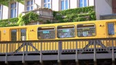 BERLIN, GERMANY - JUNE 24, 2019: Yellow BVG U-Bahn Metro Train In Front of A House With Beautiful Vine Climbing Plants In Berlin, Germany