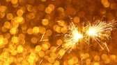 fajerwerki : Sparkler burning against Golden Christmas or New Year festive background