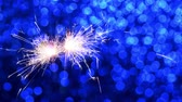 fajerwerki : Sparkler burning against Blue Christmas or New Year festive background