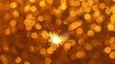 ハイライト : Sparkler burning against Golden Christmas or New Year festive background