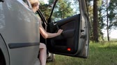 Girl out the car door in forest 4k Stock Footage