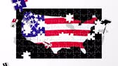 bayrak : Puzzle pieces fly in and form a map of the USA with a billowing stars and stripes stenciled behind the outline of the country. Stok Video