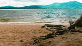 quiet : Waves crashing gently on quiet sandy beach. mountain background. 4K footage Stock Footage