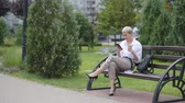 ベンチ : Coffee break. Business woman sitting in the park on a bench, working with a phone