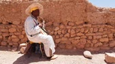 kasbah : AIT BENHADDOU, MOROCCO- MAY 04: Unidentified man playing traditional moroccan instrument on May 04, 2013 in Ait Benhaddou, Morocco. The place is declared UNESCO heritage site.