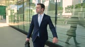 Businessman in a suit in a hurry, hi is late, looking at the watch. Steadicam shot. Dostupné videozáznamy
