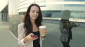 Pretty girl walking and using app on smartphone drinking coffee. Steadicam shot.