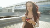 Pretty girl walking and using app on smartphone drinking coffee in the sun. Steadicam shot. Dostupné videozáznamy