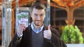 куш : Happy man holding in his hand bundles of money cash Euro and showing thumbs up