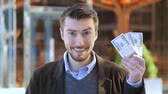 куш : Happy man holding in his hand bundles of money cash dollars and showing thumbs up