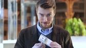 куш : Attractive man leafing through a bundle of dollars, looking at camera and smiling