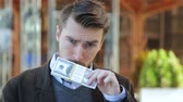 куш : Attractive man leafing through a bundle of dollars, smelling cash, looking at camera and smiling