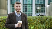 Attractive man drinking coffee or tea from paper cup, smiling Dostupné videozáznamy