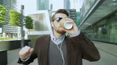 Attractive man putting on headphones, listening to music, walking, dancing, drinking coffee from a paper cup