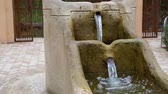 achtertuin : old vintage water fountain with streaming water, classical village architecture Stockvideo