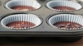 bakeware : Sprinkling chocolate chips onto cupcake batter already in baking pan