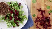 saláta : Adding toasted sunflower seeds to salad with cress, beets and sunflower seeds