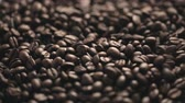кофе в зернах : Whole coffee beans falling onto pile, close up.