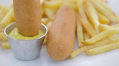 rántott : Dipping corn dog into metal condiment cup of mustard with french fries on the side