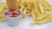 rántott : Dipping corn dog into metal condiment cup of ketchup with french fries on the side