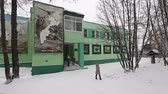 lour : YELIZOVO CITY, KAMCHATKA, RUSSIA - JAN 5, 2017: Winter view of office building of Kronotsky Nature Biosphere Reserve; adults and children coming out of building after visit to Museum of Nature.