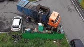 municipal services : PETROPAVLOVSK KAMCHATSKY CITY, KAMCHATKA PENINSULA, RUSSIA - AUG 16, 2018: Top view on driver of garbage truck KAMAZ loading municipal container with garbage into its bins with help of manipulator.