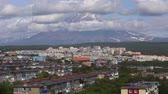 longe : Summer townscape of Kamchatka Peninsula: view of urban development of Petropavlovsk-Kamchatsky City on background of volcano clouds floating across the sky, around rocky mountains on sunny day. Time lapse Stock Footage