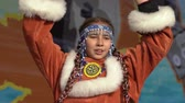 абориген : KAMCHATKA PENINSULA, RUSSIA - NOV 4, 2018: Girl dancing in national clothing indigenous inhabitants Kamchatka. Concert, celebration of Koryak national ritual holiday Hololo (Day of Seal). Slow motion.