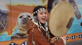 абориген : KAMCHATKA PENINSULA, RUSSIA - NOV 4, 2018: Young woman in national clothing indigenous inhabitants Kamchatka beats tambourine and sings. Celebration of Koryak national holiday Hololo (Day of Seal).