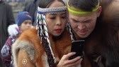 domorodý : KAMCHATKA PENINSULA, RUSSIA - NOV 4, 2018: Young woman dancer in national clothing indigenous inhabitants Kamchatka reads messages in smartphone, and young man looking into her phone.