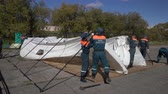 спасение : KAMCHATKA PENINSULA, RUSSIA - OCT 2, 2018: Group of rescuers Kamchatka Rescue Center Emercom of Russia setting up an army field tent, deploy campground on windy day. All-Russian civil defense training