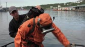 KAMCHATKA PENINSULA, PACIFIC OCEAN, RUSSIAN FAR EAST - 5 SEP, 2018: Sailor removes black gas cylinder (air balloon) from professional scuba diver in orange diving suit after long work underwater.