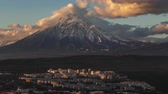 Kamchatka Peninsula time lapse: evening top view of stunning cityscape of Petropavlovsk-Kamchatsky City on background clouds drifting across sky and cone of active Koryaksky Volcano. Kamchatka Region, Russian Far East, Eurasia.