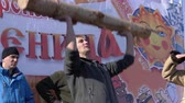 halter : YELIZOVO CITY, KAMCHATKA PENINSULA, RUSSIA - MARCH 10, 2019: Russian fun - man raises birch log over his head during folk festivities on Maslenitsa - religious, folk holiday, celebrated during last week before Great Lent.