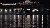 отраженный : KAMCHATKA PENINSULA, RUSSIAN FAR EAST - 10 MAY, 2019: Dark night view of stately Expedition Passenger Cruise Liner Norwegian Jewel (NCL) sailing in Pacific Ocean. Porthole lights reflected in sea. Стоковые видеозаписи