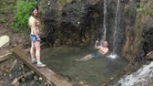 gyógyulás : KAMCHATKA PENINSULA, RUSSIA - JUNE 12, 2019: Couple young travelers take therapeutic, medicinal baths in outdoor pool natural hot springs with geothermal mineral water having balneological properties