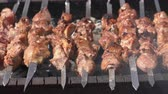 rôti de porc : Grilled appetizing juicy pork shish kebab cooking on metal skewers on charcoal grill with fragrant fire smoke. Close-up view, selective focus on pieces of delicious roast meat. Cooking summer picnic